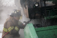 Firefighter sprays down tractor fire